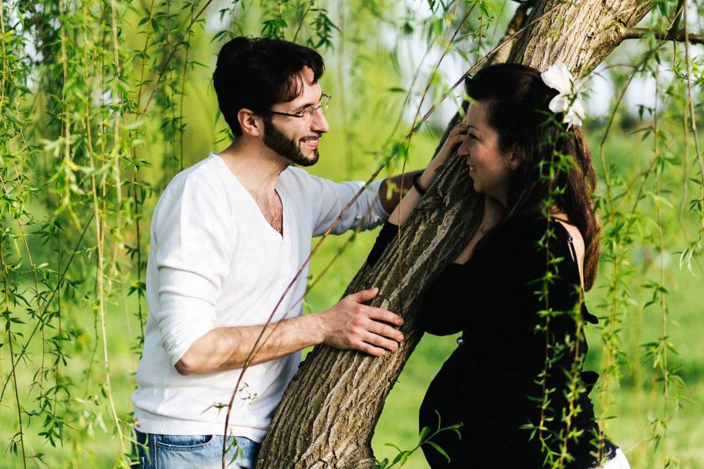 foto gravidanza all'aperto coppia vicino ad un albero