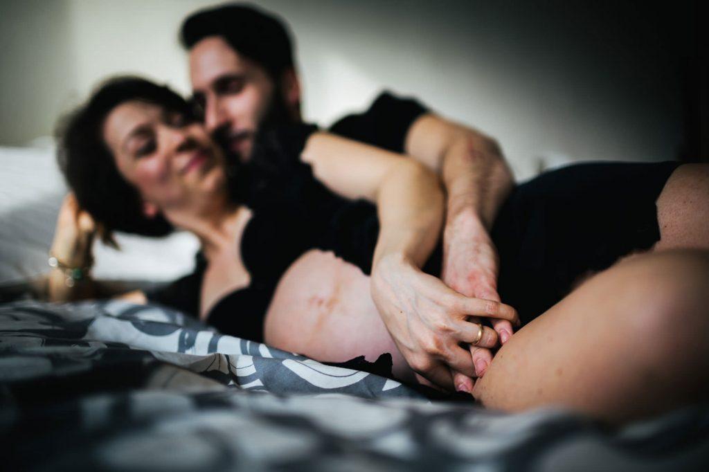 foto gravidanza mamma e papà che si abbracciano sul letto